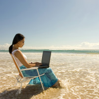 Asian woman with laptop getting wet..